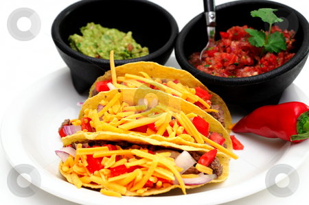 Tacos stock photo, Three corn tortilla tacos with ground beef, tomatoes, onions and cheddar cheese with bowls of salsa and guacamole on the side by Lynn Bendickson