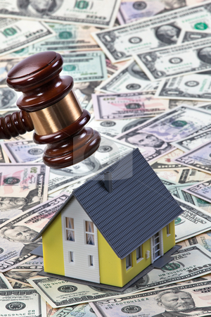 Toy House with Currency stock photo, Toy house being hit by gavel surrounded by American currency. Vertically framed shot. by Erwin Johann Wodicka