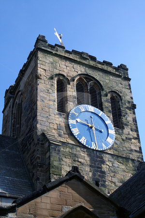 Church clock tower stock photo, Low angle view of Christian church clock tower with blue sky background. by Martin Crowdy