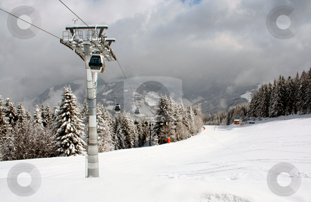 Ski lift in Alps mountains stock photo, Scenic view of aerial ski lift and gondola cars in Swiss Alps mountains with forest in background. by Martin Crowdy