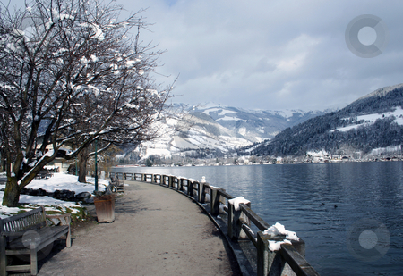 Snowy alpine lake stock photo, Scenic view of path around lake with snow capped mountains in background, Zeller See, Zell am Zee, Austria. by Martin Crowdy