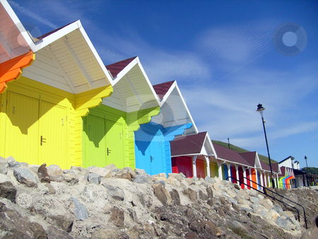 Seaside beach chalets stock photo, Low angle view of colorful seaside beach chalets or huts. by Martin Crowdy