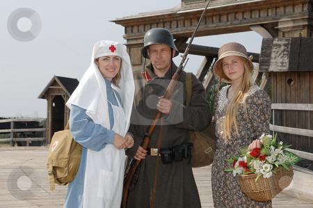 Retro styled picture with two womens and soldier stock photo, Old style picture with woman in nurse costume, her daughter in flowered dress and man in soldier uniform with weapon. Costumes are authentic to the ones weared in time of  World War I. by Roberts Ratuts