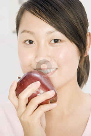Smiling Woman Holding Apple stock photo, Close-up of a young woman about to eat a red apple.  She is smiling at the camera.  Vertically framed shot. by Paul Burns