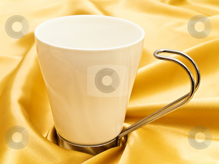 white mug stock photo, Photo of single white mug at the golden fabric drapery by Sergej Razvodovskij