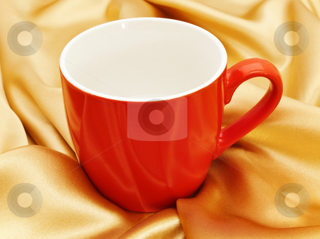 Red mug stock photo, Photo of single red mug at the golden fabric drapery by Sergej Razvodovskij