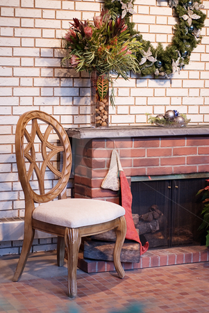 Fireplace with wreath stock photo, A cozy view of a wooden chair sitting by a brick fireplace by Richard Nelson