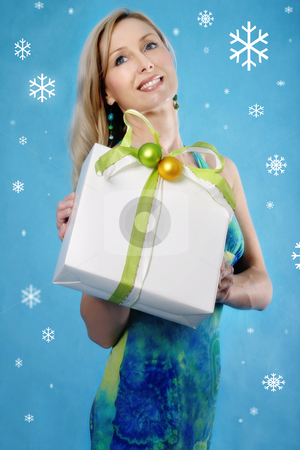 Seasons Greetings - woman holding wrapped gift stock photo, Smiling woman holding a wrapped parcel present on a blue winter background by Leah-Anne Thompson