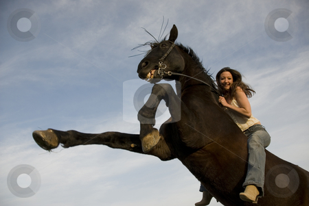 Happy girl and rearing stallion stock photo, Happy girl and rearing stallion in blue sky by Bonzami Emmanuelle