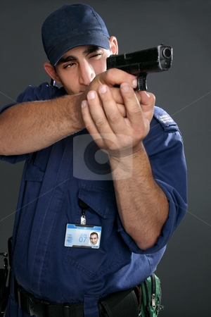 Security Officer takes aim stock photo, Security guard taking aim with gun.  Please note:  Badge photo is same person and was photographed by me.  No extra release required. by Leah-Anne Thompson
