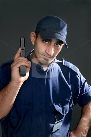 Security Officer stock photo, Watchful security officer in uniform, holding a gun. by Leah-Anne Thompson