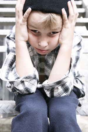 Street Kid stock photo, Depressed street kid sits on a fire escape stairs of grungy backlane building. Cool filter and some added contrast for effect. Focus on face. 
