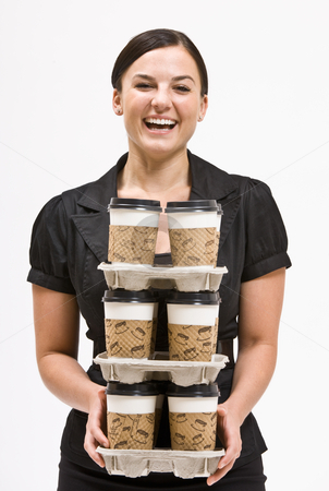 Businesswoman carrying stack of coffee cups stock photo, Businesswoman carrying stack of coffee cups by Jonathan Ross