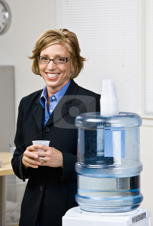 Businesswoman getting water from water cooler stock photo, Businesswoman getting water from water cooler by Jonathan Ross