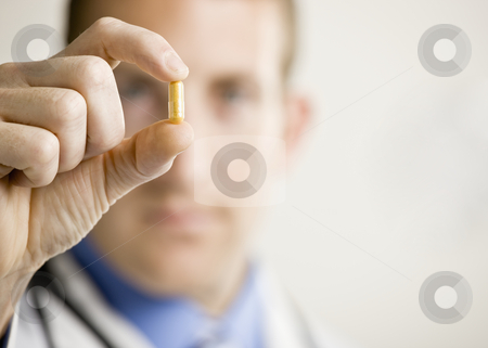 Young Male Doctor stock photo, Young male doctor holding medication. Horizontally framed shot. by Jonathan Ross