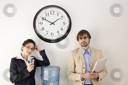 Businesspersons at Water Cooler stock photo, Male and female businesspersons talking under clock. Horizontally framed shot. by Sean De Burca