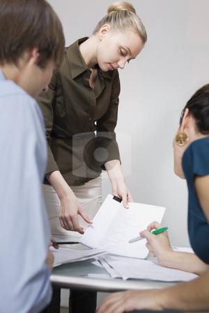 Businesspeople with Paperwork stock photo, Businesspersons discussing paperwork. Vertically framed shot. by Sean De Burca