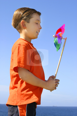 Pinwheel in the breeze stock photo, A child with a spinning pinwheel on a bright beautiful day by Leah-Anne Thompson