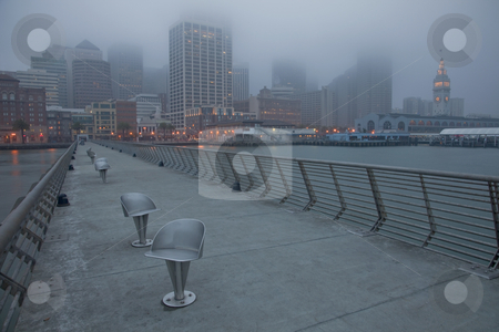 San Francisco skyline on a foggy morning stock photo, San Francisco cityscape with Ferry Terminal at down shot from Pier 14 with metal swivel chairs, top of buidlings disappearing in fog and low clouds before winter sunrise by Marek Uliasz