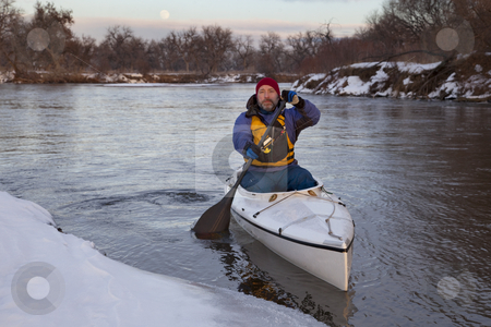 Paddling canoe on a winter river stock photo, Mature male paddling a decked expedition canoe on river in winter scenery (South Platte in eastern Colorado) by Marek Uliasz