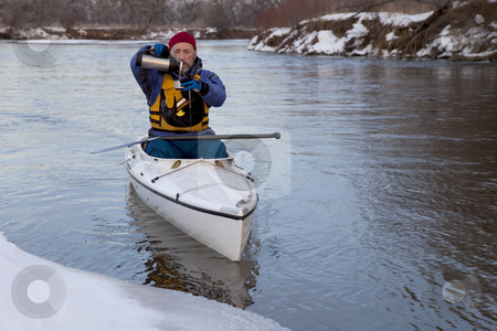 Winter canoe - break for hot tea stock photo, Winter canoe paddling on icy river, taking a break for hot tea (South Platte River in eastern Colorado) by Marek Uliasz