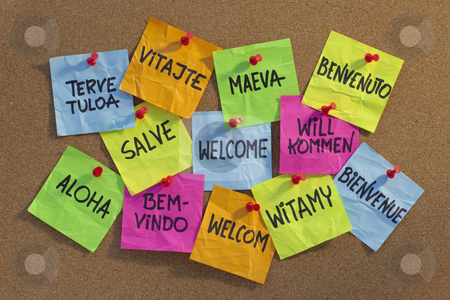 Welcome, willkommen, bienvenue, aloha, ... stock photo, Welcome in a dozen of languages (Finnish, Slovak, Tahitian, Italian, Latin, English, German, Hawaian, Portuguese, Dutch, Polish, French) - cloud of colorful sticky notes on cork bulletin board, low angle contrasty light by Marek Uliasz