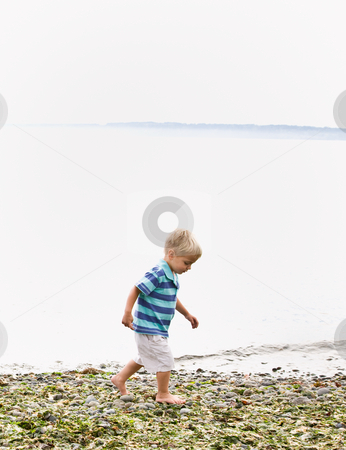 Boy walking near ocean at beach stock photo, Boy walking near ocean at beach by Jonathan Ross