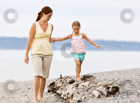 Mother helping daughter walk on log at beach stock photo, Mother helping daughter walk on log at beach by Jonathan Ross