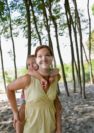 Mother giving daughter piggy back ride stock photo, Mother giving daughter piggy back ride by Jonathan Ross