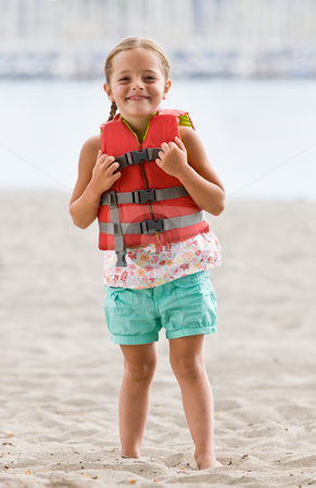 Girl wearing life jacket at beach stock photo, Girl wearing life jacket at beach by Jonathan Ross