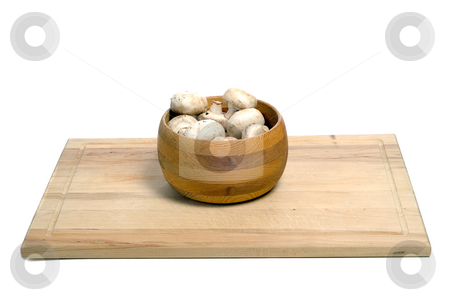 Bowl Of Mushrooms stock photo, A wooden bowl of aged mushrooms shot on a wood cutting board, isolated against a white background by Richard Nelson