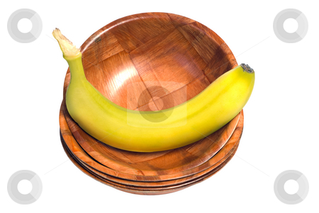 Banana In A Bowl stock photo, A fresh banana sitting in a wooden bowl, at the top of a stack of bowls, isolated against a white background by Richard Nelson