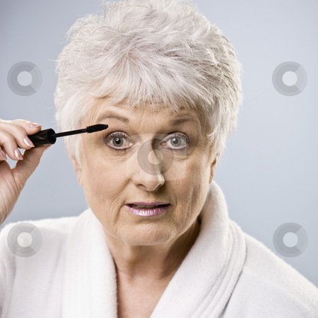 Older Woman Putting on Makeup stock photo, Older woman putting on makeup. Square framed shot. by Jonathan Ross