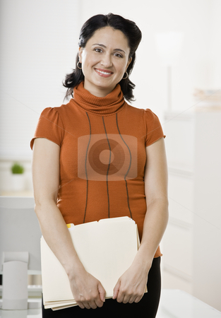 Businesswoman with Paperwork stock photo, Portrait of business woman with paperwork and file folders. Vertically framed shot. by Jonathan Ross