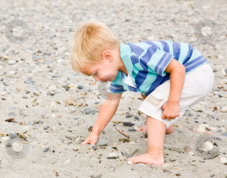 Boy gathering rocks at beach stock photo, Boy gathering rocks at beach by Jonathan Ross
