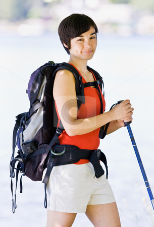 Woman hiking with backpack and walking stick stock photo, Woman hiking with backpack and walking stick by Jonathan Ross