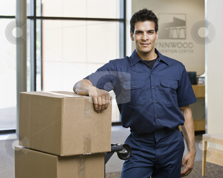Young Man Standing With Boxes stock photo, Young man standing next to stack of boxes.  Horizontally framed shot. by Jonathan Ross