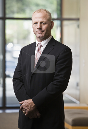 Businessman in Suit stock photo, Businessman in suit, standing with hands folded. Vertically framed shot. by Jonathan Ross