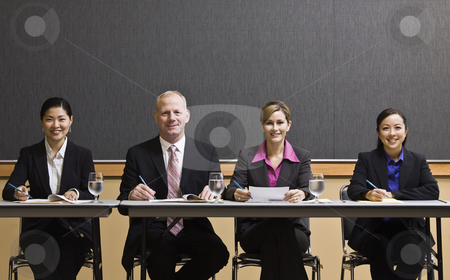Business People Sitting at Table stock photo, Business people smiling, sitting at table.  Horizontally framed shot. by Jonathan Ross
