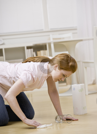 Young Woman Cleaning Floor stock photo, Young woman cleaning up spill from floor. Vertically framed shot. by Jonathan Ross