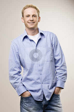 Young Man Smiling stock photo, Young man standing and smiling at camera.  Vertically framed shot. by Jonathan Ross