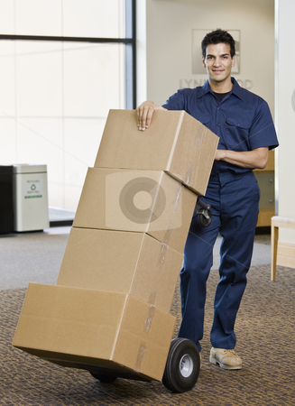 Young Man Moving Boxes stock photo, Young man using hand truck to move boxes.  Vertically framed shot. by Jonathan Ross