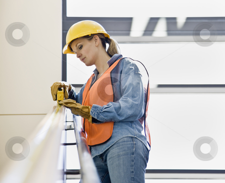 Female Construction Worker stock photo, Female construction worker taking measurement with measuring tape.  Horizontally framed shot. by Jonathan Ross