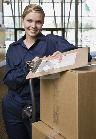 Young Woman Delivering Boxes stock photo, Young woman using hand truck to deliver boxes with delivery forms.  Vertically framed shot. by Jonathan Ross