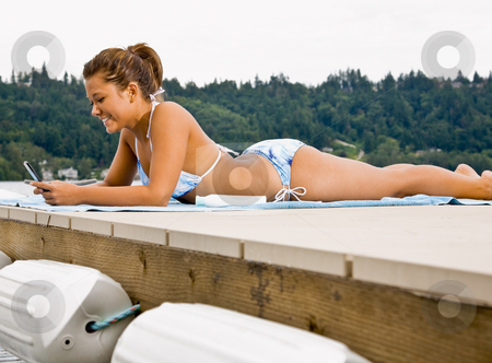 Woman laying on pier text messaging on cell phone stock photo, Woman laying on pier text messaging on cell phone by Jonathan Ross