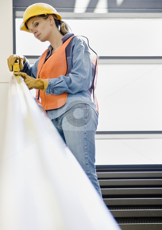 Female Construction Worker stock photo, Female construction worker taking measurement with measuring tape.  Vertically framed shot. by Jonathan Ross