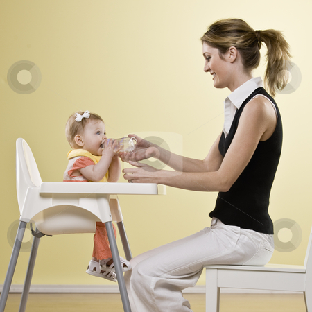 Young Woman and Baby Girl stock photo, Young woman feeding bottle to baby girl in high chair.  Square framed shot. by Jonathan Ross