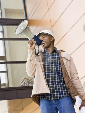 Male Construction Worker Using Bullhorn stock photo, Male construction worker using bullhorn. Vertically framed shot. by Jonathan Ross