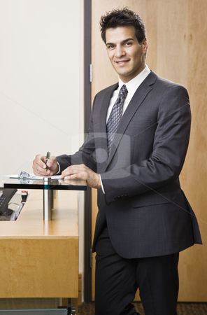 Young Businessman Smiling stock photo, Businessman smiling standing next to reception desk.  Vertically framed shot. by Jonathan Ross