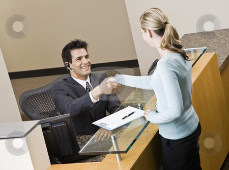 Businesswoman and Receptionist stock photo, Businesswoman shaking hands with receptionist.  Horizontally framed shot. by Jonathan Ross